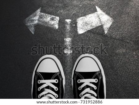 Making decisions concept. Sneakers on the asphalt road with drawn arrows pointing to two directions.  #731952886