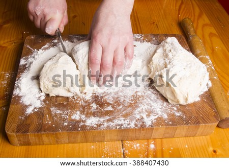 Making dough by female hands on wooden table background - Shutterstock ID 388407430