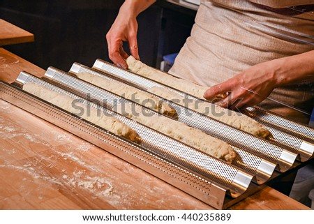 Making dough by female hands on wooden table background. preparing in bakery. baguette on a metal baking tray #440235889