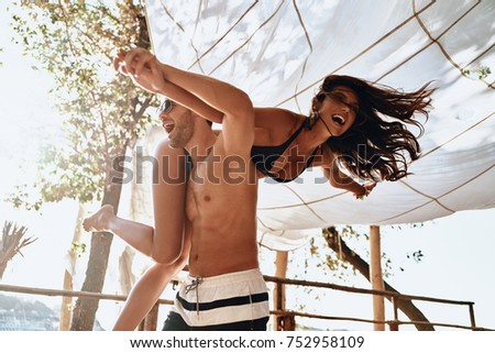 Making each other happy. Handsome young man carrying young attractive woman on shoulders while spending carefree time on the beach outdoors