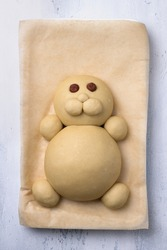 Making Easter Bunny Buns of delicious sweet dough for a child. Do it yourself. Step by step instruction. Step 3. Make a muzzle of dough  - а cheeks and a nose, of nuts - an eyes