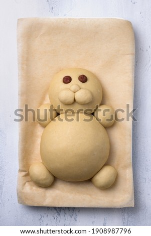 Making Easter Bunny Buns of delicious sweet dough for a child. Do it yourself. Step by step instruction. Step 3. Make a muzzle of dough  - а cheeks and a nose, of nuts - an eyes Сток-фото ©