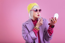 Making funny face. Cute lovely retired woman wearing pink dress making funny face coloring lips