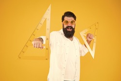Making geometry fun. Funny hipster using geometrical tools at geometry. Geometry teacher holding triangles for school lesson on yellow background. Bearded man learning or teaching geometry.