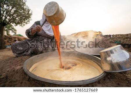 making grape molasses and raisins with traditional method. (uzum pekmezi) natural molasses. making molasses on fire. Stok fotoğraf ©