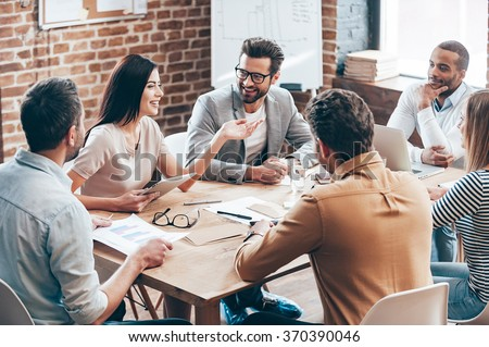 Making great decisions. Young beautiful woman gesturing and discussing something with smile while her coworkers listening to her sitting at the office table #370390046