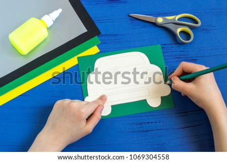 Making greeting card for Father's Day in shape of car. Children's art project. DIY concept. Step-by-step photo instruction. Step 2. Child draws car using template  #1069304558