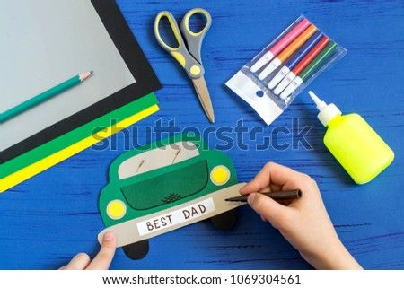 Making greeting card for Father's Day in shape of car. Children's art project. DIY concept. Step-by-step photo instruction. Step 9. Child makes inscription: Best Dad #1069304561