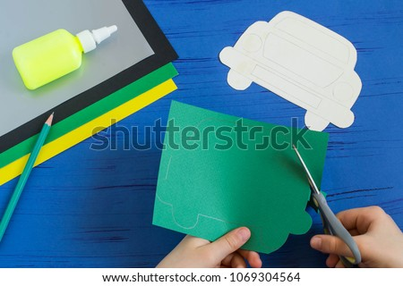 Making greeting card for Father's Day in shape of car. Children's art project. DIY concept. Step-by-step photo instruction. Step 3. Child carves card in shape of car #1069304564