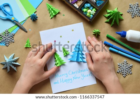 Making greeting card with origami 3D Xmas tree from paper. Merry Christmas and Happy New Year decoration. Children's DIY concept. Handmade crafts on holiday with your own hands. #1166337547