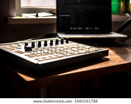 making hip hop beats on the drum machine controller at the home studio with laptop #1060161788