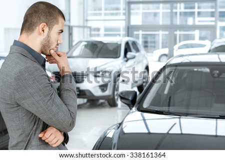 Making his choice. Horizontal portrait of a young man in a suit looking at the car and thinking if he should buy it