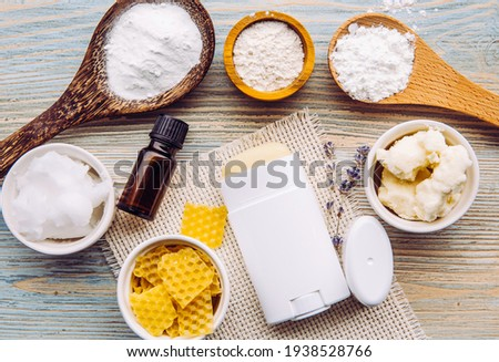 Making homemade deodorant stick with all natural ingredients concept. Blue wooden background. Ingredients: arrowroot powder, baking soda, beeswax, shea butter, essential oil, cornstarch, coconut oil.