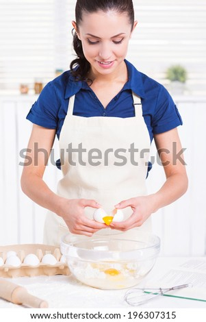 Making homemade pastry. Attractive young woman cracking egg into a bowl