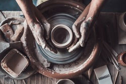 Making it together. Top view of potter teaching child to make ceramic pot on the pottery wheel