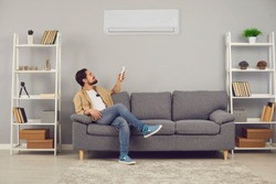 Making life easy and enjoying good, modern, convenient conditioning system at home: Relaxed young man sitting on sofa in living-room and adjusting air conditioner temperature mode with remote control