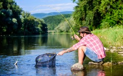 Making me happy. mature bearded man with fish on rod. successful fisherman in lake water. hipster fishing with spoon-bait. fly fish hobby of man hipster. big game fishing. relax on nature.
