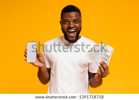 Making money on internet. Happy african-american guy showing showing cellphone with blank screen and bunch of money, orange background, free space