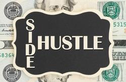 Making money with your side hustle, Side Hustle text on chalkboard on USA twenty dollar bills