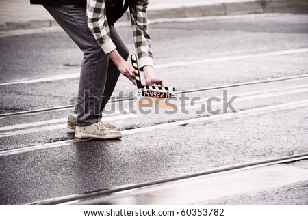 Making movie and slate holding by a man on wet road