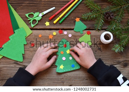 Making of handmade christmas tree from felt with your own hands. Children's DIY concept. Making xmas toys decoration or greeting card. Step 3. Decorate the toy.