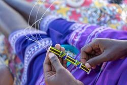 Making of handmade jewellery. Masai african women hands, top view, close up. Island of Zanzibar, Tanzania, East Africa