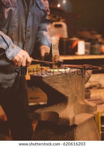 Making of horseshoe. Male worker with hammer making nail holes on horseshoe. #620616203