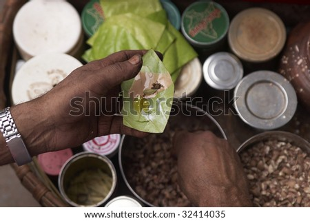 Making Paan  in Delhi, India. Areca nut and spices wrapped in a betel leaf which is chewed and then spat out.