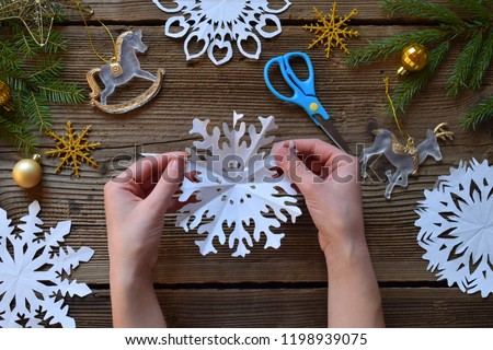 Making paper snowflakes with your own hands. Children's DIY. Merry Christmas and New Year concept. #1198939075