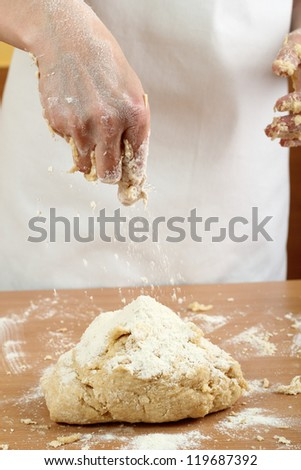 Making Pastry Dough for Hungarian Cake. Series. A baker pouring flour on dough.