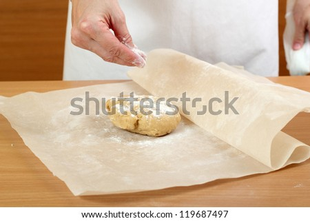Making Pastry Dough for Hungarian Cake. Series. A baker rolling a dough between sheets of baking paper.