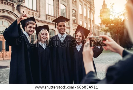 Making photo of graduates in mantles standing near university and smiling.