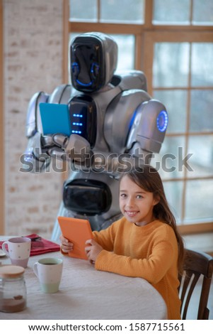 Making picture. Robot with a tablet in his hands standing and making pictures