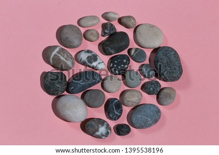 making picture with stones . top view photo. isolated pink background.