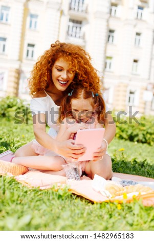 Making pictures. Beautiful red haired woman expressing positivity while looking at her gadget