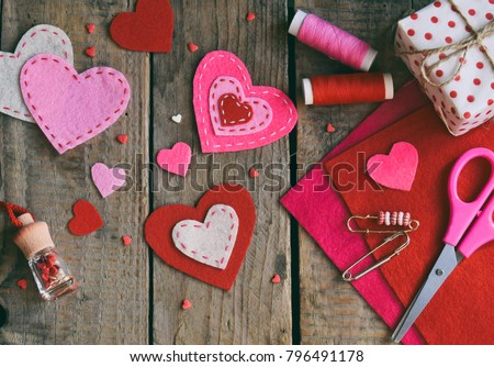 Making pink and red hearts of felt with your own hands. Valentine's Day background. Valentine gift making, diy hobby. Children's DIY concept. Making heart decoration or greeting card. Handmade concept