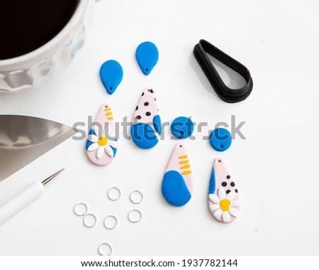 making pink blue and white daisy flower polymer clay earrings with 3D printed clay cutter tools Foto stock ©