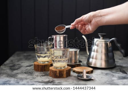 Making pour over coffee with condensed milk Vietnamese style. Woman hand pouring ground coffee into phin on dark background copy space #1444437344