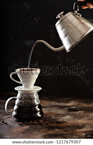 Making pour over coffee with hot water being poured from a kettle #1217679307