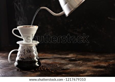 Making pour over coffee with hot water being poured from a kettle #1217679310