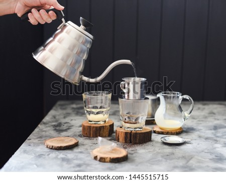 Making pour over Vietnamese milk coffee. Woman hand pouring water from goose neck kettle into phin on dark background copy space #1445515715