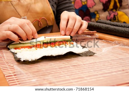 Making rolled sushi in a bamboo sushi mat stock photo