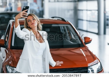 Making selfie. Woman in formal clothes is indoors in the autosalon.