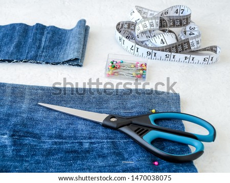 Making shorts out of blue jeans with multi colored headed sewing pins, white tailor tape with centimeters and inches and scissors. Shorten the jeans. DIY shorts out of jeans. Top view.