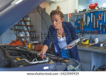Making some adjustments to her car. Portrait of young female mechanic. Female mechanic fixing car.. Auto car repair service center. Repair, car service concept