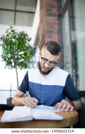 Making some notes. Bearded businessman making some notes while studying new law