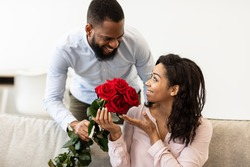 Making Surprise. Excited black girlfriend receiving bouquet of red roses from her happy boyfriend who holding bunch of flowers and greeting her with St Valentine's or International Women's Day