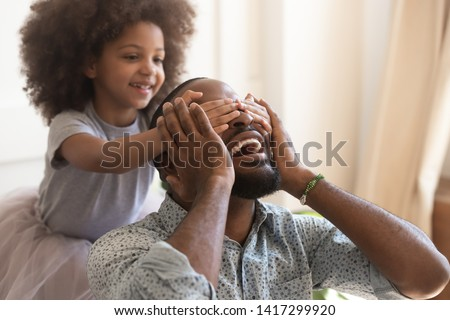 Making surprise for daddy concept, cute little african american kid daughter close eyes of excited happy black dad on fathers day, funny small child girl having fun with papa laughing bonding at home