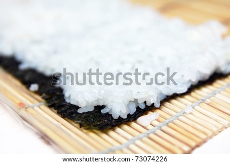 Making sushi roll on wooden mat, closeup