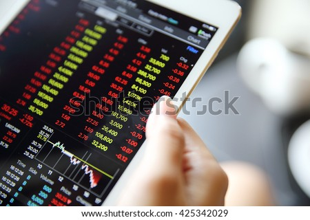 Making trading online on the tablet with bussiness woman hand #425342029